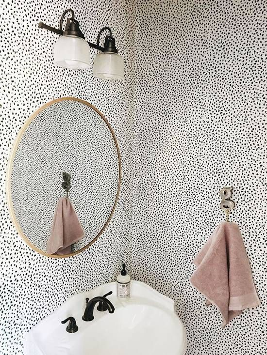 A feminine take on the graphic style, with a bold monochrome wallpaper softened with copper and dusty pink detail.