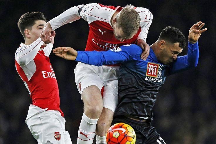 Per Mertesacker heads the ball clear under pressure from Joshua King as Hector Bellerin looks on