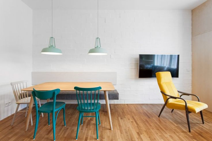 Opposite the cooking area sits a dining table with two mint-coloured suspended lampshades hanging from the ceiling, next to the armchair and lounge area by the window.