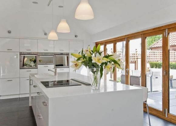 Contemporary kitchen in gloss white with built-in storage large central island and bi-fold doors to garden entertaining space