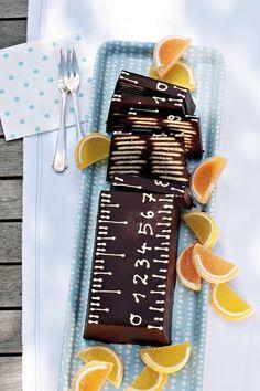 Kekskuchen Maßarbeit für die Kinderparty: mit Schokolade umhüllte Orangenkekse, in der Kastenform (mit Klarsichtfolie ausgelegt) geschichtet und fest werden lassen. Stürzen, Folie abziehen und mit weißer Kuvertüre zu einem Lineal garnieren.  Fotograf: Burdafood.net Hans Gerlach