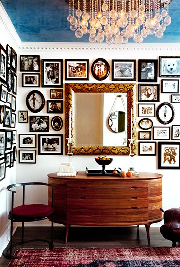 Framed black and white photos, snakeskin frame mirror, crystal drop chandelier, and walnut console table // foyers.