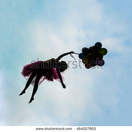 silhouette of young beautiful girl with balloons on blue sky with clouds…