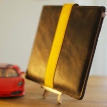 Racy 'Turbocharged' iPad leather sleeve with build-in noblesse of classic racing cars. It is hand-crafted in Munich/Bavaria from premium quality soft and strong (2 mm thick) dark brown marbled cowhide with a contrasting yellow/orange rally stripe.