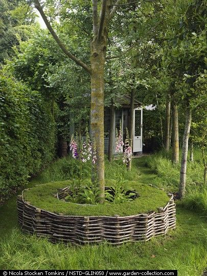 A circular tree seat made from woven hazel rods encircles the deciduous Claret Ash (Fraxinus angustifolia 'Raywood') creating a romantic, shady seat and lovely focal point
