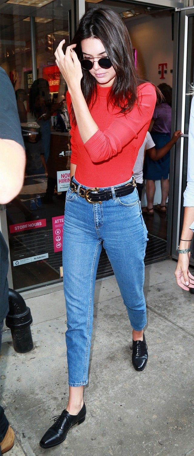 Kendall Jenner wears a red sweater, high-rise jeans, round sunglasses, oxfords, and a statement belt