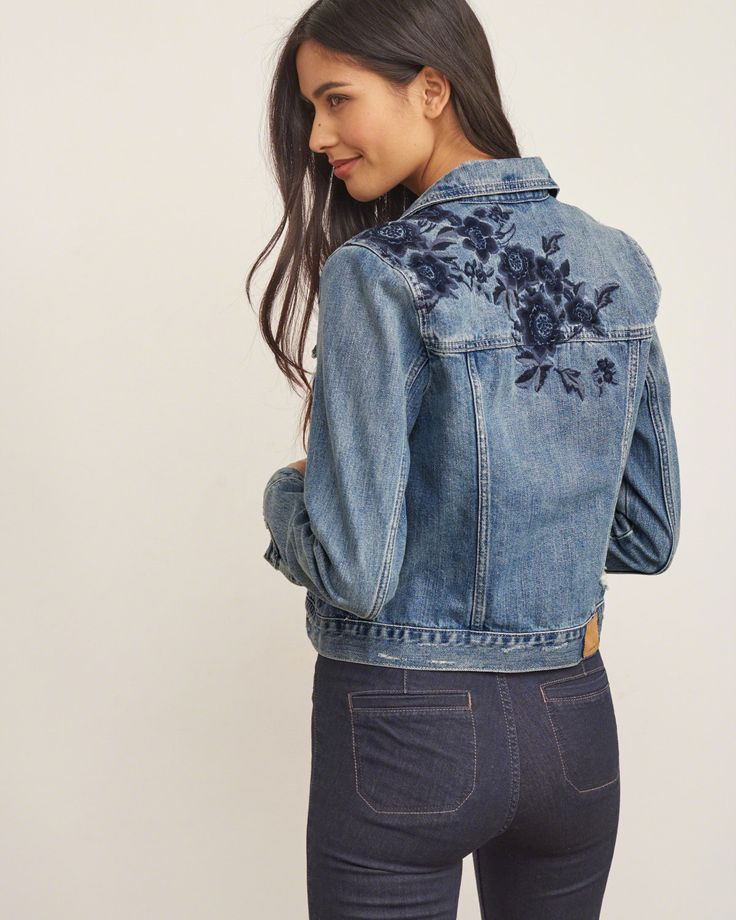Classic style in a medium wash featuring two front button chest pockets, two side welt pockets, subtle distressed details, button front and cuffs accented with tonal, and floral embroidery on shoulders and back.