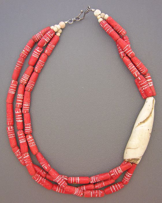 by Anne Holland |  Three strands of unusually carved red clay beads obtained from an African  trader are nested with a beautiful antique shell from Nagaland. The Naga people,  from the hills of northeast Indian and western Burma, were amazingly creative in  their adornments. |  Dorje Designs