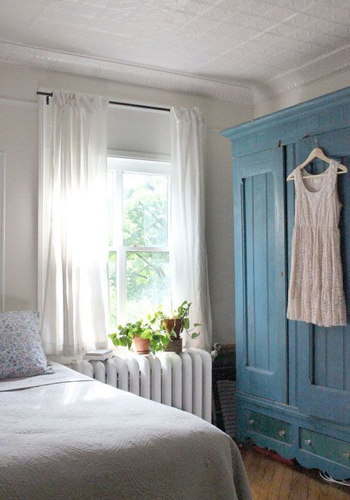Love the simple white walls and window dressing, plants on the radiator, and blue wardrobe. Very simple and calming - just the sort of feel you want for a bedroom.