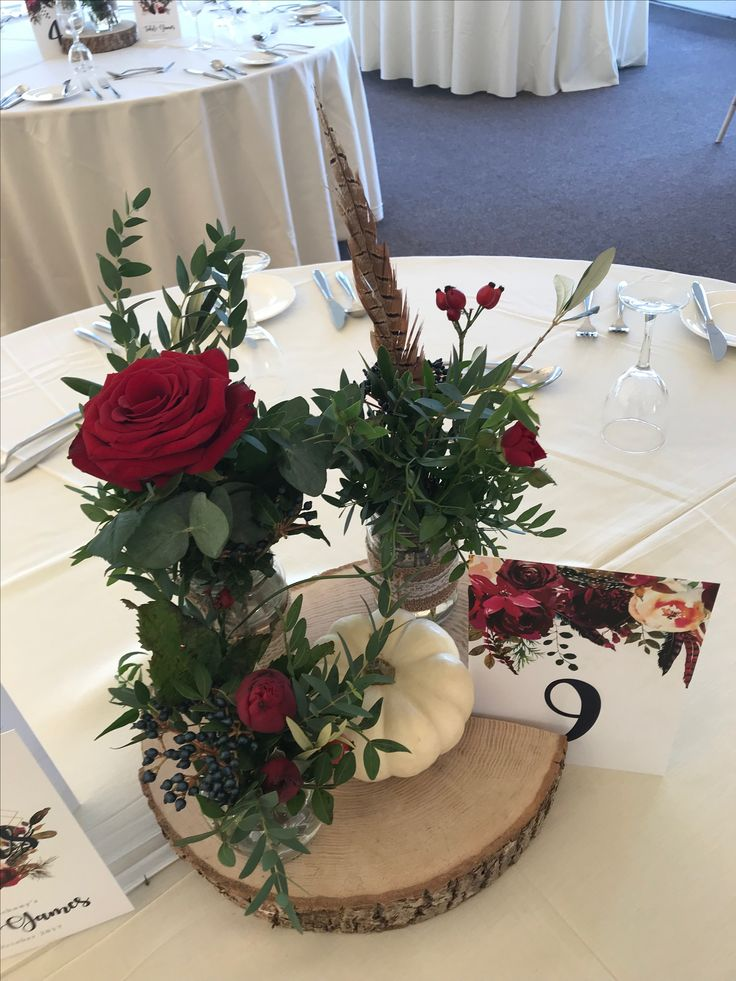 Jam Jar Arrangement: Red Roses, Red Spray Roses, Viburnum Berries, Pheasant Feathers on a log base with a Gourd