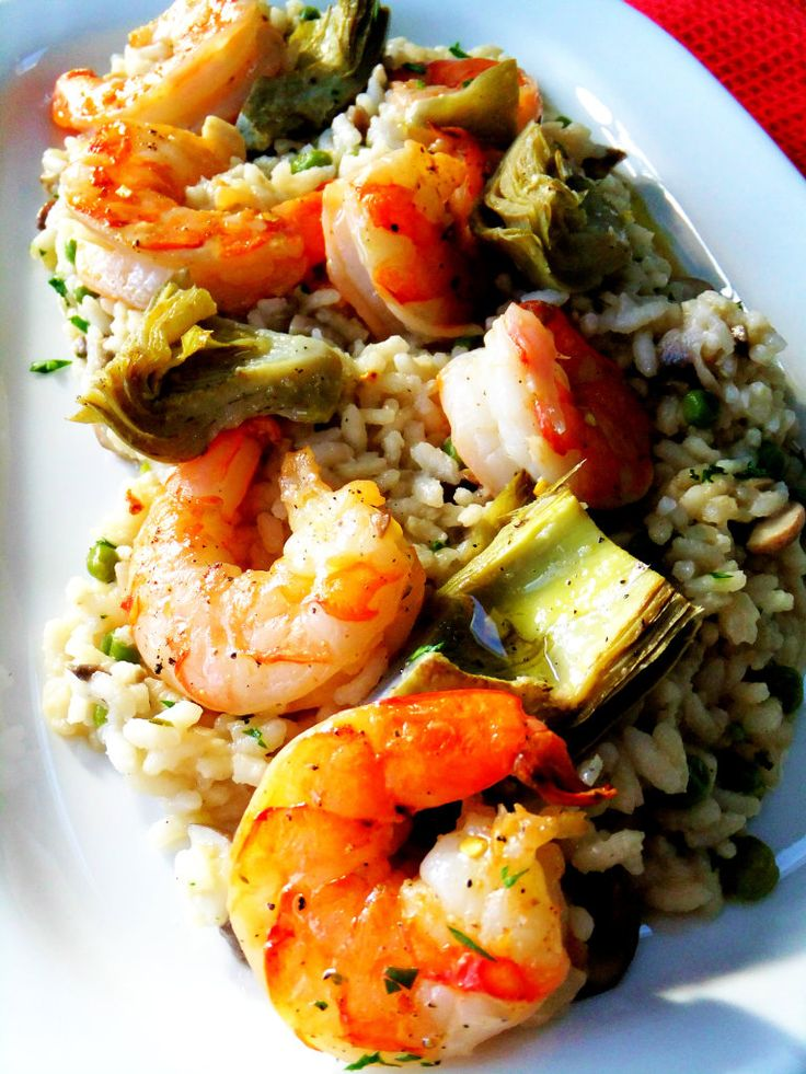 Succulent tiger shrimp with fresh artichoke hearts, sitting on a bed of creamy risotto.