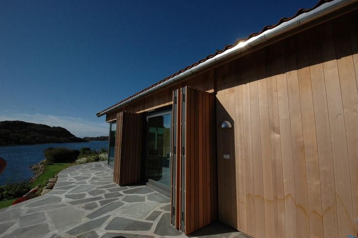 Cladding in red cedar wood.  The folding shutters in open position. Architect: Marita Hamre