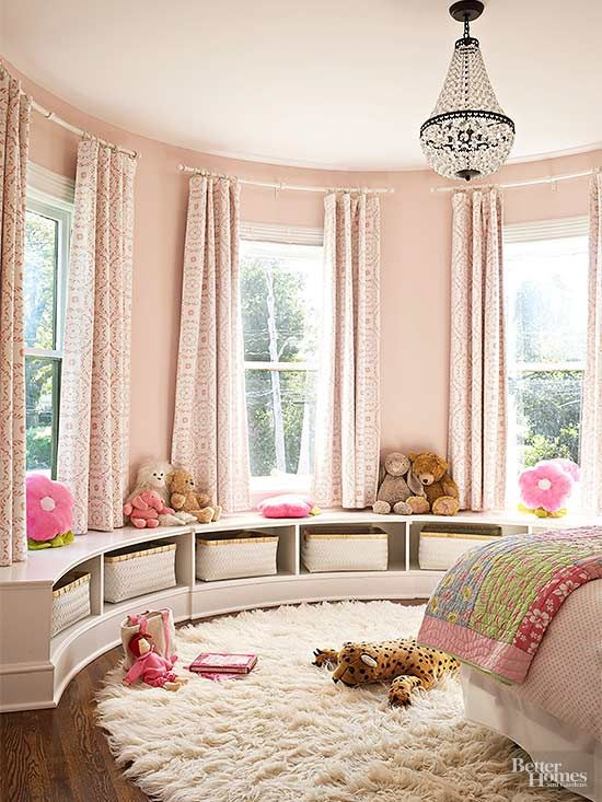 One little girl's bedroom in the top of the original turret dresses up in soft pink walls and draperies, a crystal chandelier, and flokati rug, all fit for a princess./