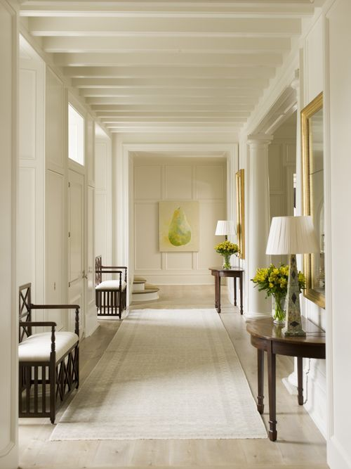 I love this long hallway with the window benches and tables/lamps on sides and center painting focus at end of hall.