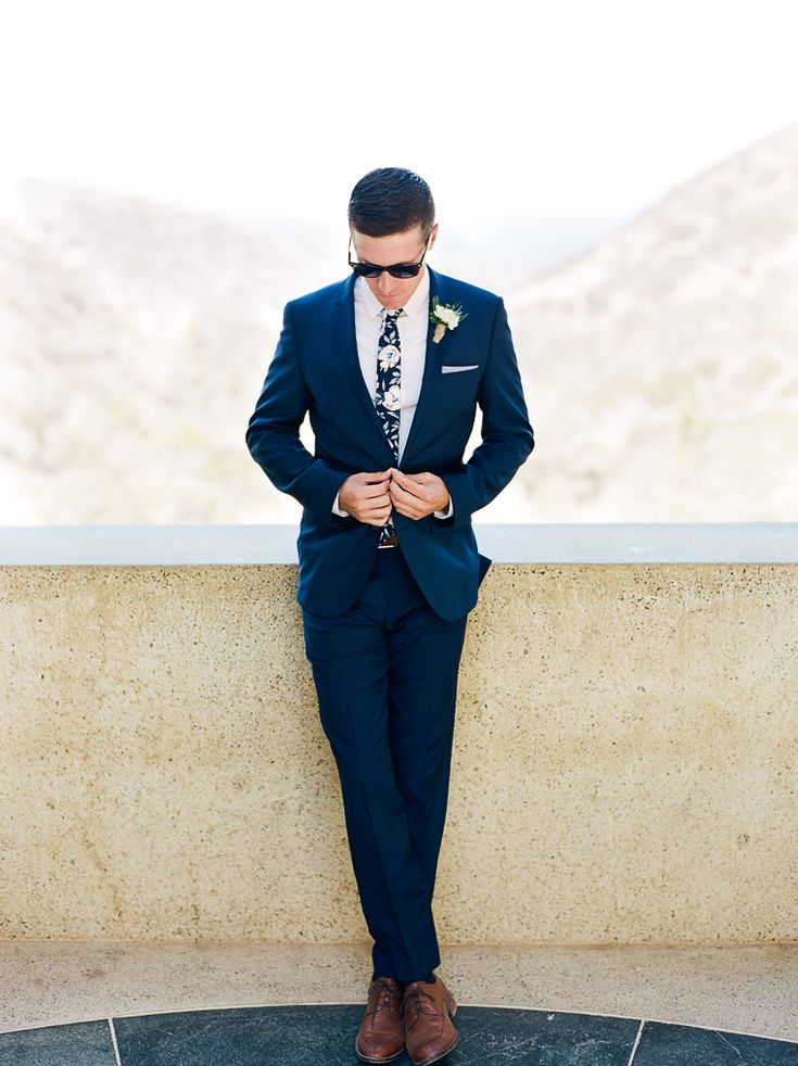 Stylish groom wearing a navy midnight blue suit by Hugo Boss and a floral print tie