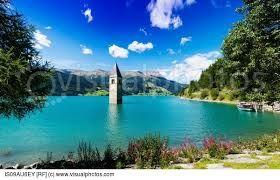 Church spire in turquoise lake, Trentino Alto Adige, Italy