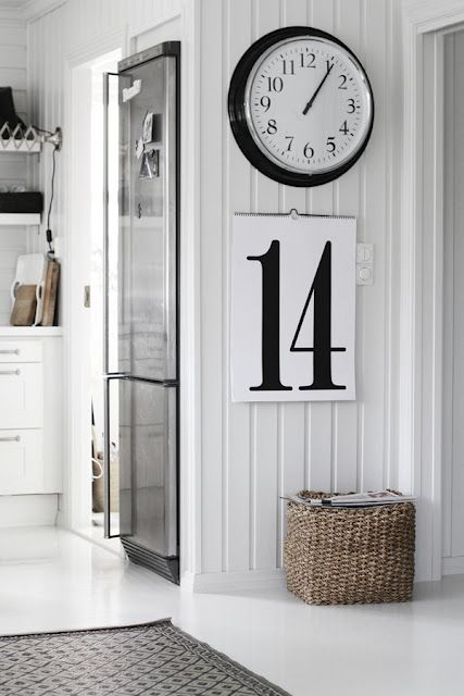 A big clock, basket and calendar may be simple items in and of themselves, but they look fabulous together against the white panelled walls.: