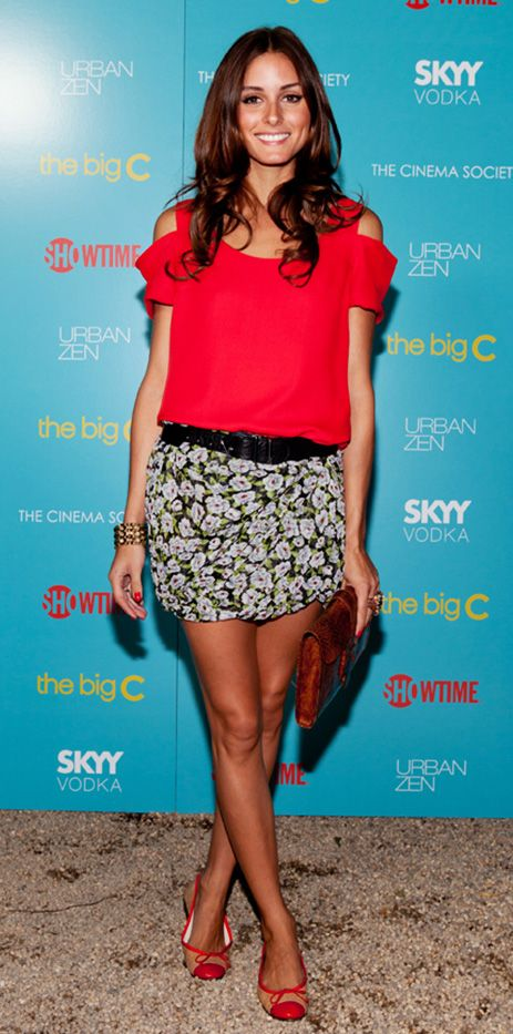 Olivia Palermo pairs a floral skirt with a black belt, red top, red clutch, and red ballet flats