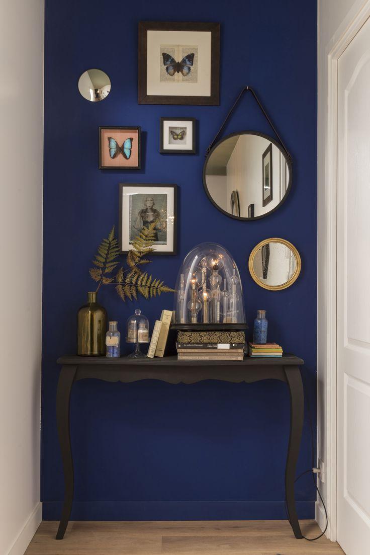 Un mur bleu profond habillé de cadres de différentes tailles