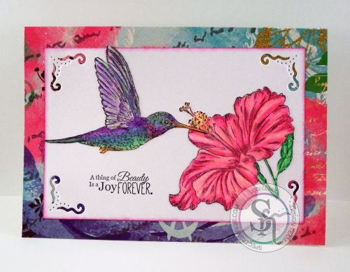 Designed by Jodi Clark for . Sheena Douglass Tropical Nectar stamp set (hummingbird, flower, sentiment). Colored with Spectrum Noir AquaBlend watercolor pencils. Flower – Soft Red, Petunia, Rose, Watermelon, Straw, Chrome Orange Leaves – Parakeet, Verdant Green, Bright Green. Hummingbird – Parakeet, Verdant Green, Crocus, Hyacinth, Carmine, Deep Blue, Regal Blue, Carrot, Mango. #spectrumnoir #sheenadouglass #crafterscompanion #craft #handmade #hummingbird #nature #colouring #watercolour