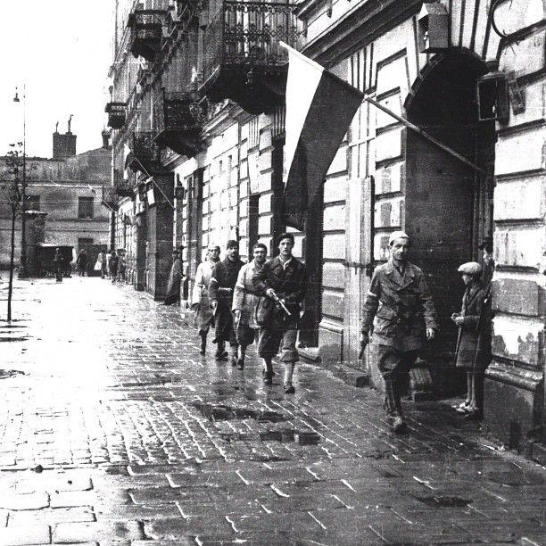"August 1st 1944, Warsaw, Casimir The Great Square, insurgents of ""Pięść"" battalion on patrol. Source: Wikimedia Commons. Photo by Stefan Bałuk."