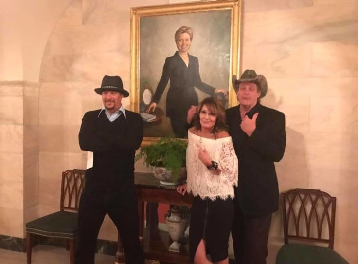 Sarah Palin, Ted Nugent, and Kid Rock pose in front of an official portrait of Hillary Clinton at the White House in April, 2017.  The irony is delicious.