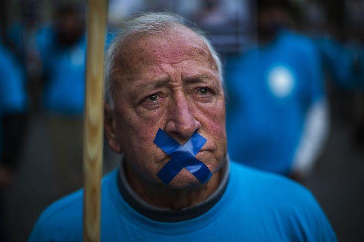 """IlPost - Barcellona, Spagna - Un ex impiegato della compagnia telefonica spagnola """"Telefonica"""" partecipa a una manifestazione dei lavoratori dell'azienda contro i licenziamenti, il 17 dicembre 2013 (AP Photo/Emilio Morenatti)"""
