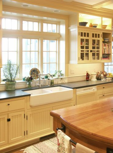 Kitchen with cream beadboard cabinets, grey counter and farmhouse sink