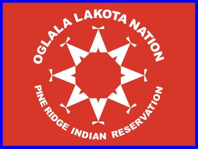 Flag of the Oglala Lakota Nation - The circle of eight teepees on the flag represent the nine districts of the reservation: Porcupine, Wakpamni, Medicine Root, Pass Creek, Eagle Nest, White Clay, LaCreek, Wounded Knee, and Pine Ridge. The red field represents the blood shed by the tribe in defense of their lands