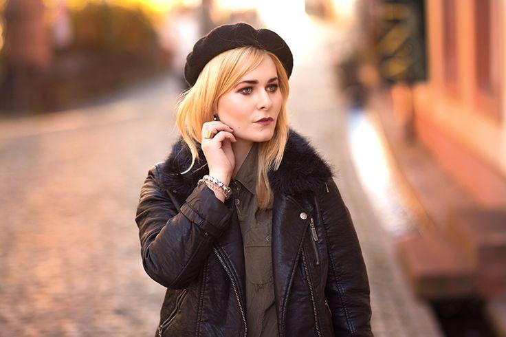Christina Key trägt einen bordeux farbenen Mini Rock mit einer Bluse in khaki und eine schwarze Lederjacke. Auf dem Kopf trägt sie eine schwarze Baskenmütze, auch Franzosen Mütze genannt