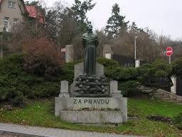 Es una estatua de Jan Hus, al lado de la calle  Elišky Přemyslovny. Es cerca de la plaza y  cerca de la inglesa Husův sbor.