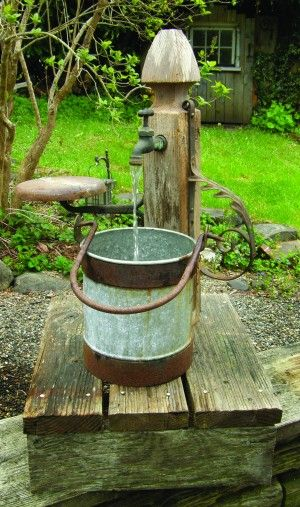 This water feature is the very essence of found object art, made  as from a table leg, a rusty bucket and iron remnants, probably  from an old buggy. So cute to use in the garden!!