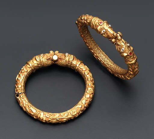 India | Pair of antique 'Makara Head' bangles | Gold with rubies | ca. early 19th century, South India | Each hinged gold bangle finely engraved to depict foliate motifs to the front, the reverse engraved in a cross-hatch pattern to the makara-head terminals with ruby detail