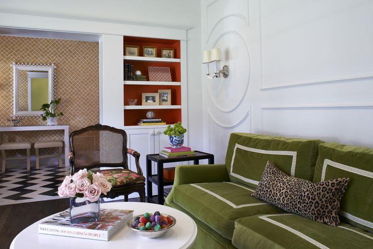 We love this chic green velvet with greek key trim on the sofa and bright orange bookshelves. by Wolfe Design House