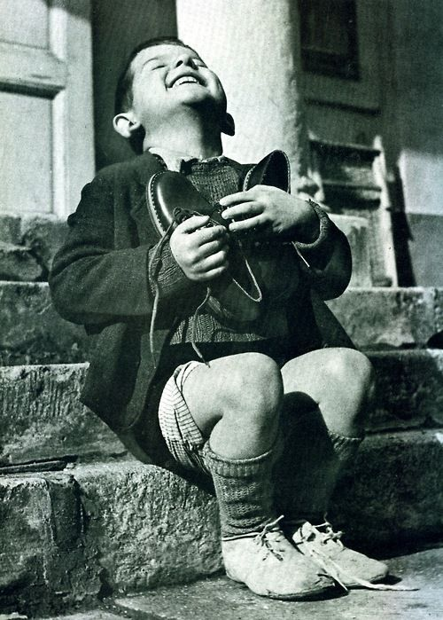 Gerald Waller - A New Possession:A six-year-old orphan from Austria (above) ecstatically embraces a brand-new pair of shoes just given to him by the Red Cross, 1946
