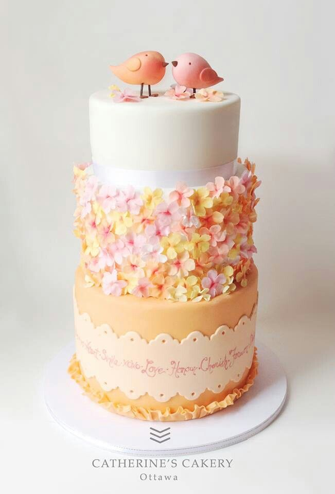 Wedding Cake - two sweet love birds on a tall light coral and white wedding cake.