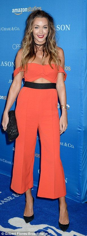 Bright at night: Courtney Sixx turned heads at the event after arriving in a bright orange jumpsuit with flared cropped pants and a bra top that she wore off-the-shoulders