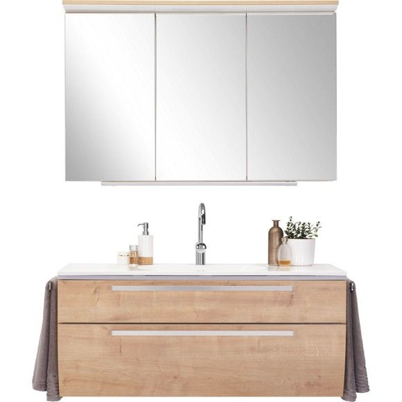 Mit dieser Möbelkombination schaffen Sie ein stilvolles Ambiente im Bad. Die freundlich wirkenden Fronten in Eichefarben sorgen für einen natürlichen Look, während edelstahlfarbene Kanten ausdrucksstarke Akzente setzen. Auf einer Breite von ca. 120 cm starten Sie Ihr morgendliches Hygieneritual: Ihre Zahnbürste sowie Ihr Make-Up für den Tag finden Sie hinter den 3 Spiegeltüren des Hängeschranks. Nachdem Sie Ihre Zähne geputzt haben