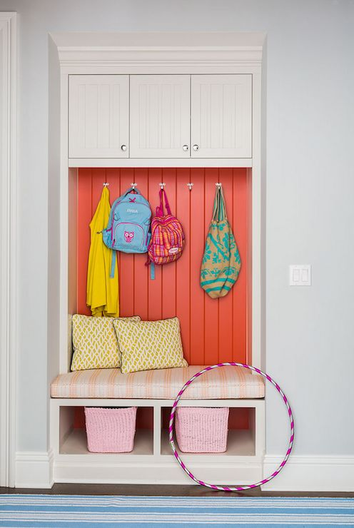 Small mudroom nook is filled with built-in cabinets with beadboard doors suspended over a built-in bench adorned with white and orange stripe cushion with storage filled with pink baskets and an orange beadboard backsplash alongside a Dash & Albert Sail Stripe Blue Woven Cotton Rug.