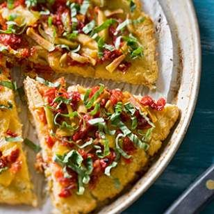 """In this healthy, gluten-free cauliflower """"pizza"""" recipe, shredded cauliflower is mixed with mozzarella and oregano to make a flourless crust that echoes the flavor of a traditional pizza pie."""