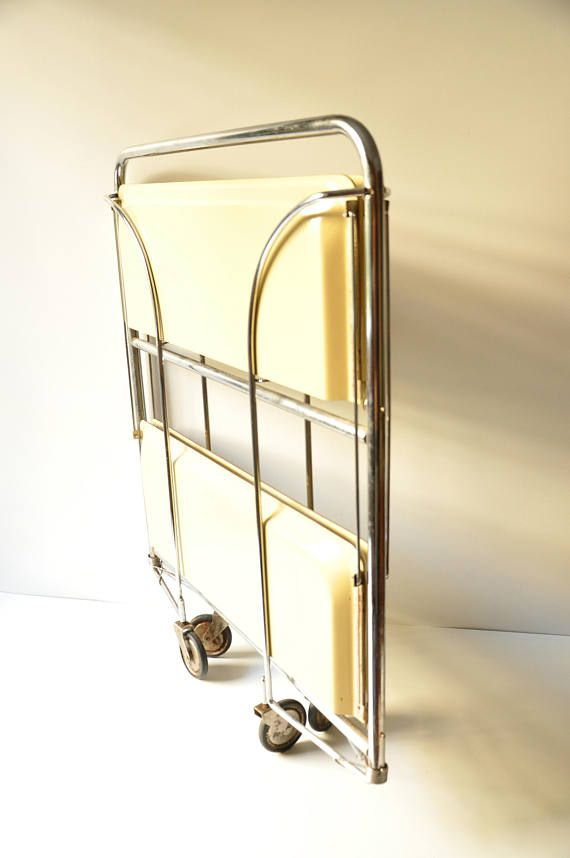 A fabulous folding bar trolley, made in Germany, in cream colour, with casters that features classic mid-century modern design and ingenious engineering: chrome brackets allow it to be folded completely flat or open only one side for use as a display shelf. This piece is perfect for so many uses! It can be folded in half against a wall for display or opened to add storage or used as a bar cart which can easily be moved from place to place. Its in very good vintage condition. The casters work…