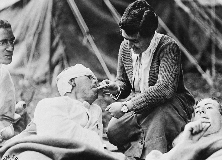 Private Ernest Stambash, Co. K, 165th Infantry, 42nd division, receives a cigarette from Miss Anna Rochester, American Red Cross volunteer at Evacuation Hospital No. 6 and 7, at Souilly, Meuse, France, on October 14, 1918.