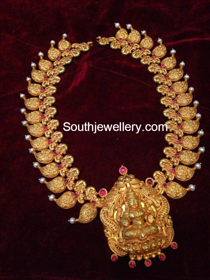 22 carat gold antique finish traditional mango and peacock design necklace with Goddess Lakshmi pendant adorned with rubies. Related PostsLakshmi Necklace with pearlsAntique Gold Haram with Lakshmi PendantLakshmi Pearl PendantLakshmi Mango Motifs NecklaceNakshi Peacock NecklaceAntique Gold Necklace with Lakshmi Pendant