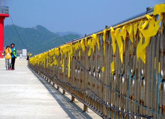 沈没現場近くの港で、安否不明者の家族が黄色いリボンが結びつけられた防波堤を歩いていた=24日午前10時26分、韓国南西部・珍島、広島敦史撮影 ▼24Apr2014朝日新聞|生きて帰れと黄色いリボン 韓国、沈没事故後に広がる http://t.asahi.com/ekb5 #Sewol #Yellowribbons
