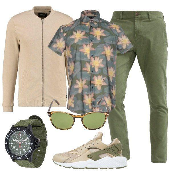 Il bomber color sabbia e i pantaloni verde oliva sono ravvivati dalla camicia a maniche corte con fantasia floreale. Gli occhiali da sole sono marroni con lenti verdi e proteggono dagli UV, al polso l'orologio con cinturino in stoffa. Le sneakers riprendono i colori del look.