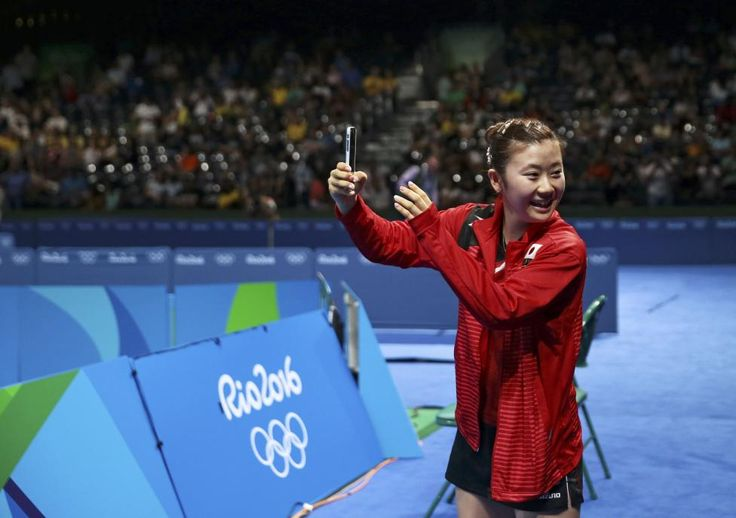Ai Fukuhara of Japan takes a picture after winning her match against Feng Tianwei of Singapore in women's table tennis quarterfinals. REUTERS/Alkis Konstantinidis