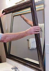 DIY Mirror Frames for a bathroom makeover. Mounting a mirror frame with double-sided tape.
