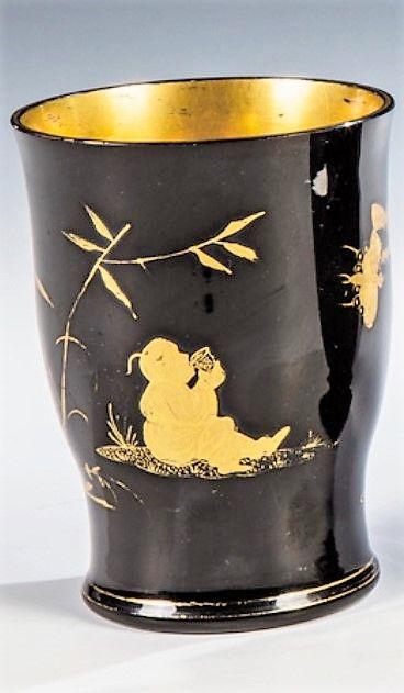 Gräflich Buquoy'sche Hütte, Georgenthal oder Silberberg, um 1825 . Steinglasbecher mit Chinoiserien  Schwarzes Hyalithglas. Auf der glockenförmigen Wandung in Matt- und Poliergold ausgeführter Dekor: unter einer Blattstaude sitzendes, aus einer Tasse trinkendes Chinesenfigürchen, fliegenden Insekten zusehend. Innen vergoldet, teils berieben. H. 10,5 cm