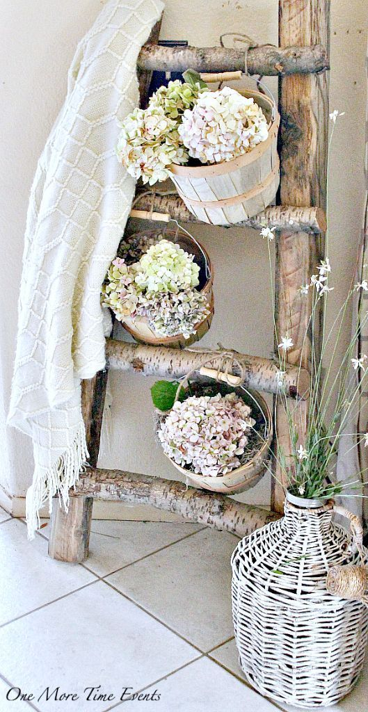 Blanket ladder decorated for summer with lighter blanket and baskets filled with hydrangeas