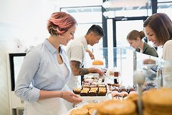 Worker serving woman pastries in bakery